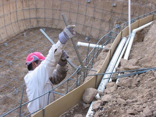 Worker Installing Rebar in an Inground Swimming Pool during construction.